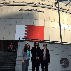Millie Chu, Diana Paez-Cook and Kristin Babbie stand in front of the Bahrain Chamber of Commerce and Industry Building.