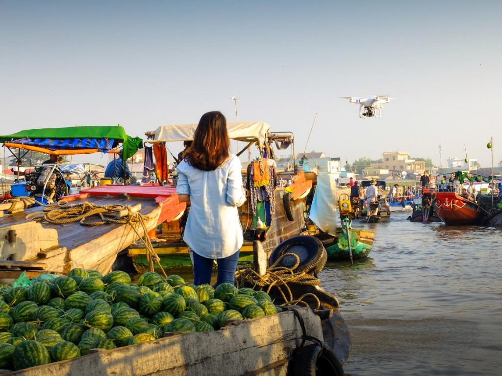 Can Tho Province, VietNam - January 28, 2015 A young girl standing on a boat, which is full of watermelons, is controlling drones to photograph how bustling floating markets Floating Cai Rang