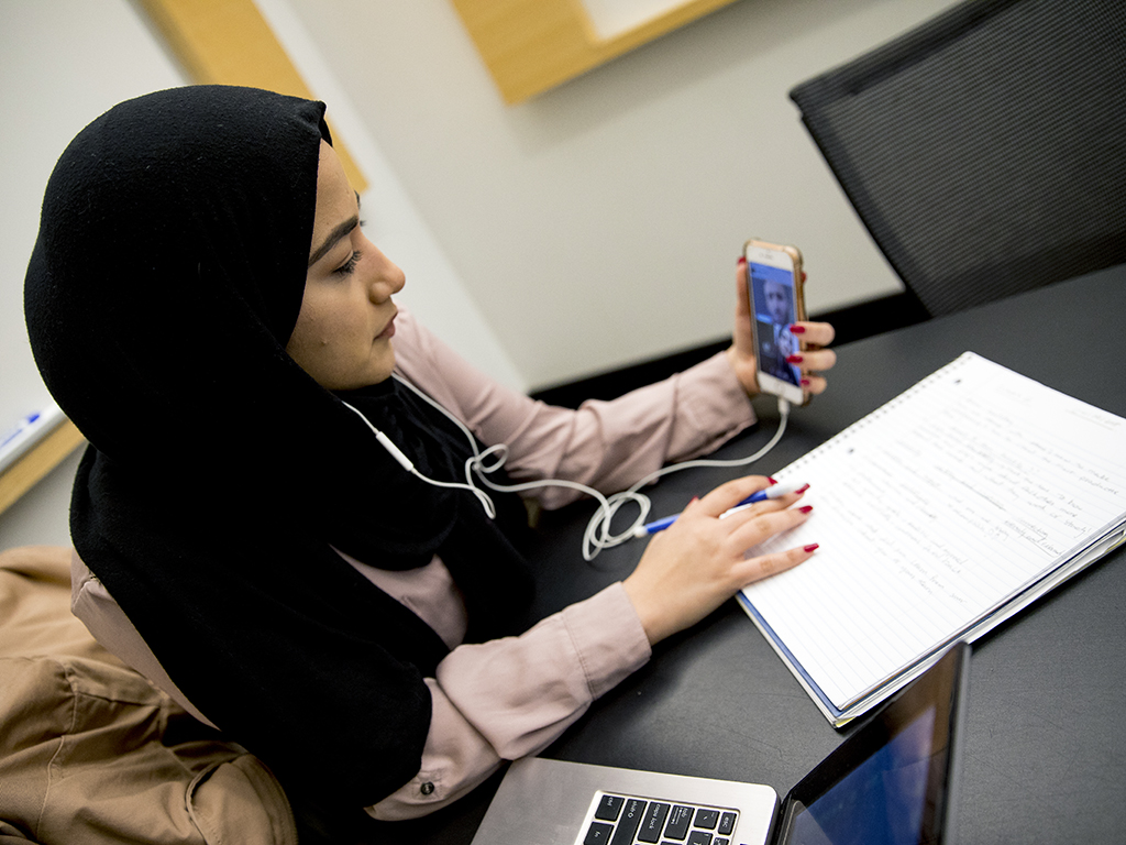 University student in the M2GATE program engaged in a video call with classmates while taking notes.